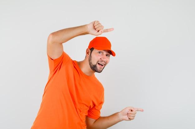 Bezorger in oranje t-shirt, pet wijst naar de zijkant en ziet er vrolijk uit, vooraanzicht.