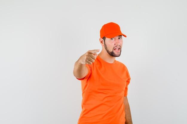 Bezorger in oranje t-shirt, pet wijzend en zelfverzekerd, vooraanzicht.