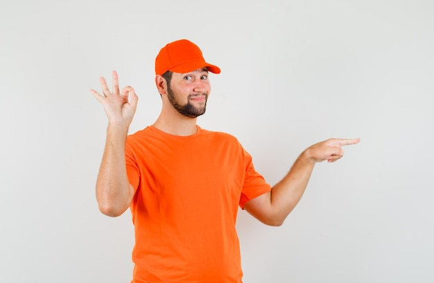 Bezorger in oranje t-shirt, pet wijzend naar de zijkant met ok-teken en vrolijk, vooraanzicht.