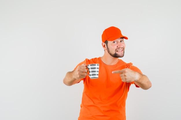 Bezorger in oranje t-shirt, pet wijzend op kopje drank en optimistisch, vooraanzicht.