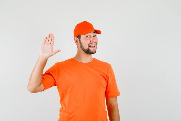 Bezorger in oranje t-shirt, pet zwaaiend met de hand om hallo of vaarwel te zeggen en er vrolijk uit te zien, vooraanzicht.