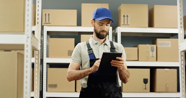 Bezorger in postwinkel met percelen en tikken op tablet-computer.