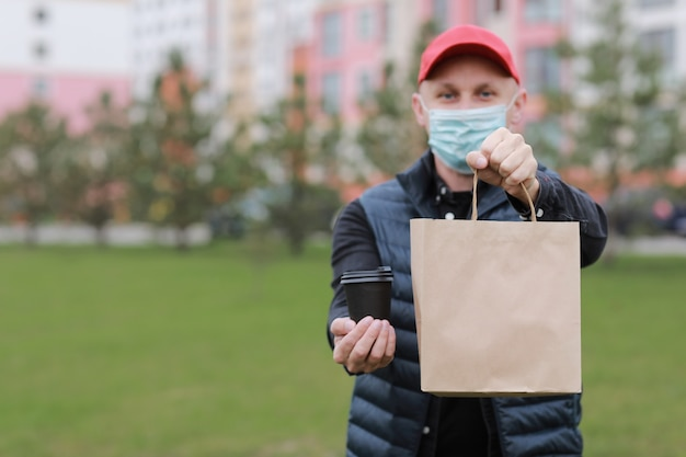 Bezorger in rode pet, gezicht medisch masker houden papieren zak weghalen en drinken in wegwerpbeker buiten in de stad