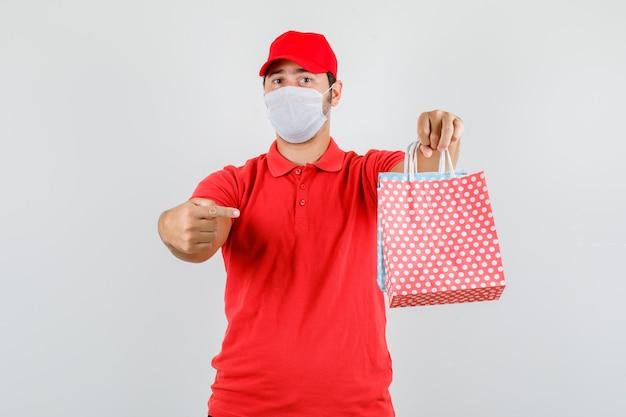Bezorger in rood t-shirt, pet, masker wijzende vinger naar papieren zakken
