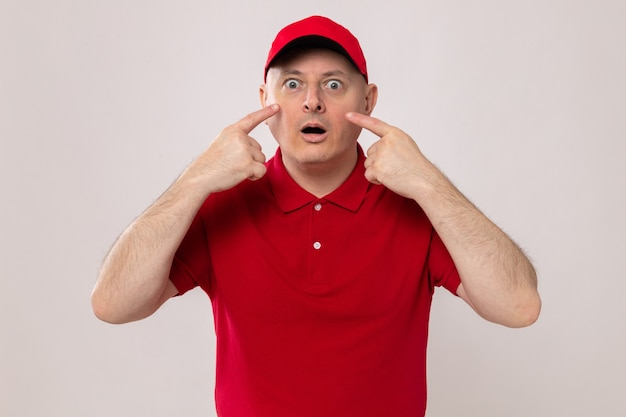 Bezorger in rood uniform en pet die verbaasd kijkt en met wijsvingers naar zijn ogen wijst