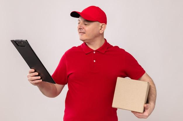 Bezorger in rood uniform en pet met kartonnen doos en klembord die ernaar kijkt glimlachend zelfverzekerd over een witte achtergrond