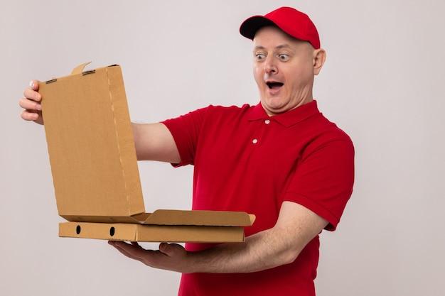 Bezorger in rood uniform en pet met pizzadozen die een van hen verbaasd en verrast opent
