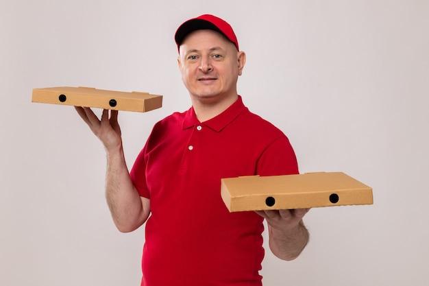 Bezorger in rood uniform en pet met pizzadozen die er glimlachend zelfverzekerd, gelukkig en positief uitziet