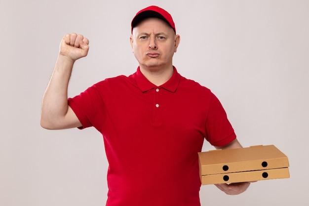 Bezorger in rood uniform en pet met pizzadozen die er met een serieuze, zelfverzekerde uitdrukking uitziet en de vuist opheft als een winnaar