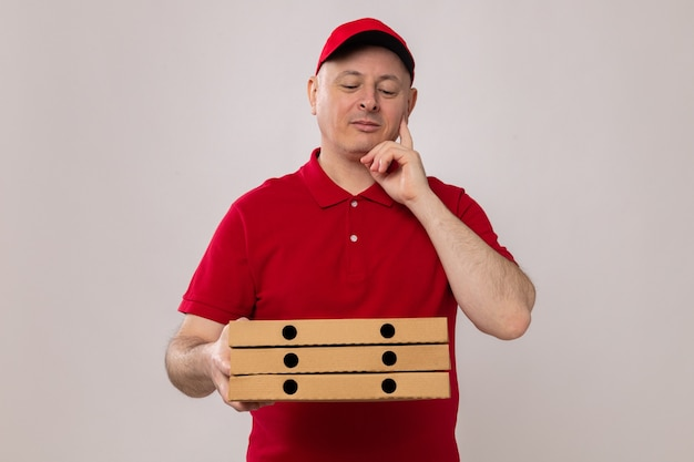 Bezorger in rood uniform en pet met pizzadozen die ernaar kijkt met een peinzende uitdrukking glimlachend positief denkend