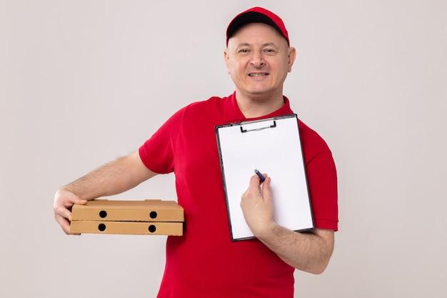 Bezorger in rood uniform en pet met pizzadozen en klembord met blanco pagina's en pen die er gelukkig en positief glimlachend zelfverzekerd uitziet