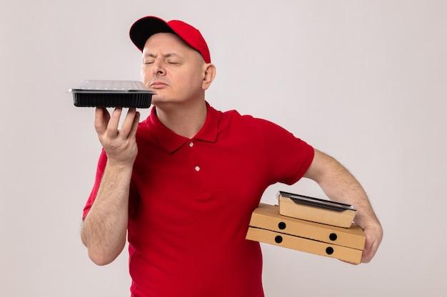 Bezorger in rood uniform en pet met pizzadozen en voedselpakketten, blij en positief, aangenaam aroma van voedsel inademend