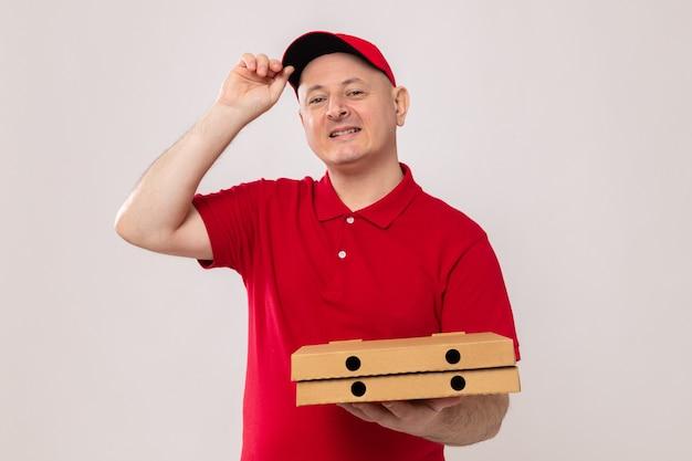 Bezorger in rood uniform en pet met pizzadozen kijkend naar camera, blij en positief glimlachend zelfverzekerd over witte achtergrond