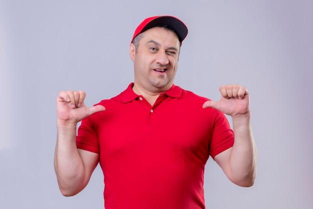 Bezorger in rood uniform en pet op zoek zelfverzekerd wijzend met beide duimen naar zichzelf trots zelfvoldaan staande over geïsoleerde witte ruimte