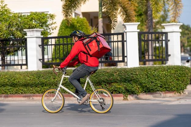 Bezorger in rood uniform fietsen om producten thuis bij klanten af te leveren.