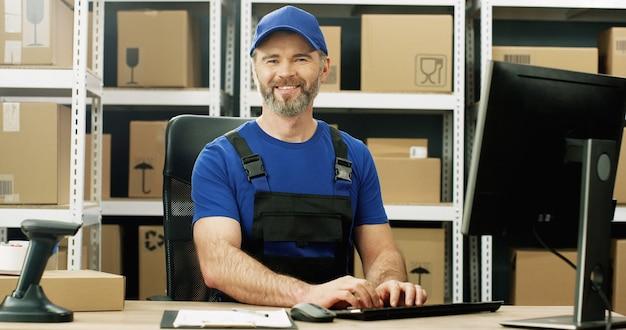 Bezorger in uniform en cap zitten aan tafel in postkantoor winkel en werken op de computer. mannelijke koerier typen op toetsenbord in opslag van pakketten.