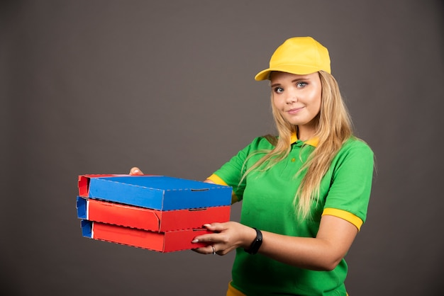 Bezorger in uniform met kartonnen pizza.