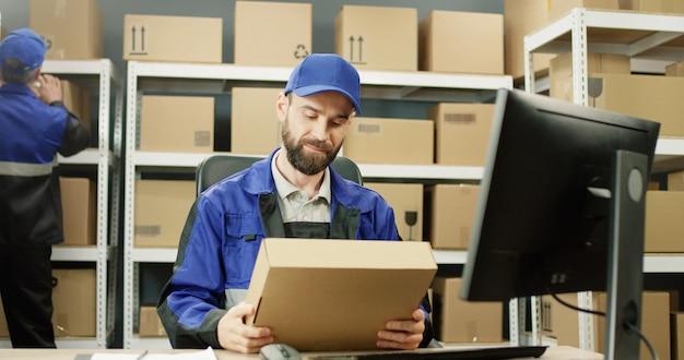 Bezorger in uniform werken op computer in postkantoor winkel met percelen.