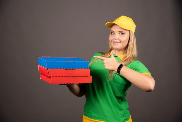 Bezorger in uniform wijzend op karton van pizza.