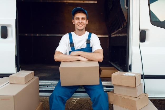 Bezorger in uniform zit tussen pakjes en kartonnen dozen, bezorgservice, bezetting bezorgen. man poseert bij kartonnen pakketten in voertuig, mannelijke bezorgen, koerier of verzending baan