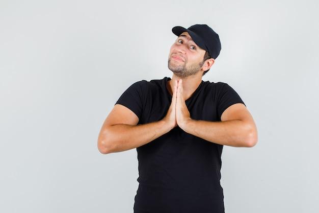 Bezorger in zwart t-shirt, pet die de handen tegen elkaar gedrukt houdt en er schattig uitziet