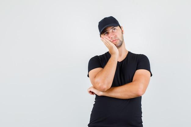 Bezorger in zwart t-shirt, pet, wang leunend op opgeheven handpalm en peinzend op zoek