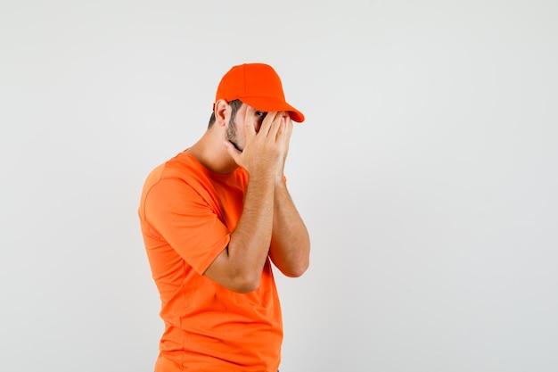 Bezorger kijkt door vingers in oranje t-shirt, pet en ziet er bang uit. vooraanzicht.