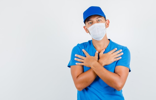 Bezorger kruising armen op de borst in blauw t-shirt, pet, masker en op zoek naar helples