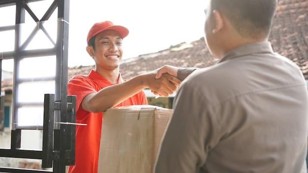 Bezorger levert de doos aan de klant en schudt de hand