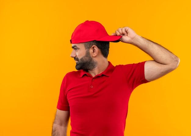 Bezorger met baard in rood uniform en pet die glimlachend opzij keek, draaide zijn pet over de oranje muur