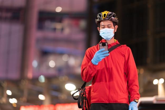 Bezorger met beschermend masker om het coronavirus te vermijden kijk naar de telefoon om het adres van de klant te vinden via de applicatie.