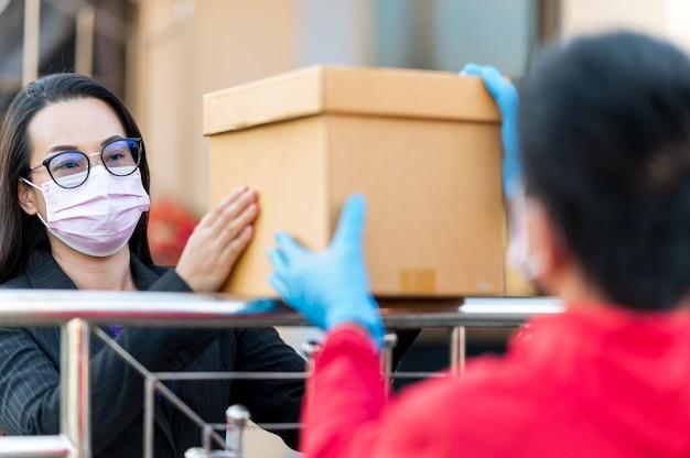 Bezorger met blauwe handschoenen bezorgt een doos aan een jonge klant bij de voordeur.