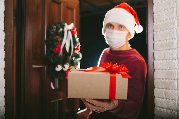 Bezorger met cadeau op kerstavond met masker van het coronavirus