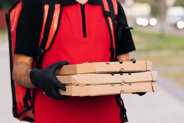 Bezorger met drie kartonnen pizzadozen bij de bezorger van straatvoedsel in de stad met een beschermend masker