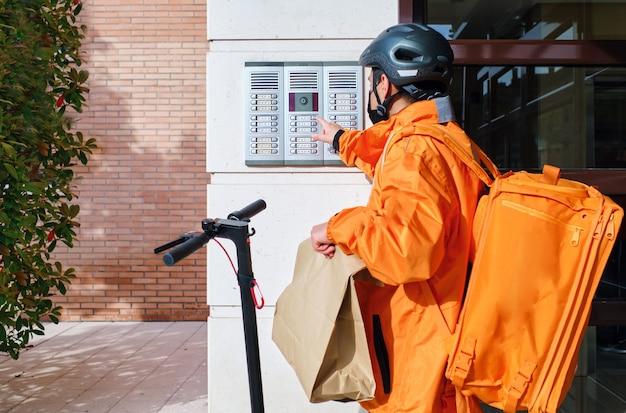 Bezorger met elektrische scooter beltijd voor thuisbezorging