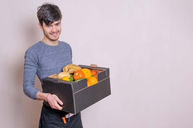 Bezorger met fruitkist in zijn handen bezorgt de bestelling, gekleed in schort en glimlachend