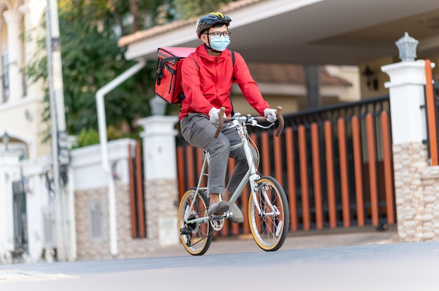 Bezorger met gezichtsbeschermend masker om coronavirus te vermijden rood uniform fietsen om producten bij klanten thuis te bezorgen.