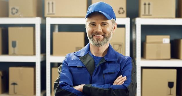Bezorger met grijze baard in blauw uniform en pet glimlachend vreugdevol in postkantoor winkel onder planken met pakketten.