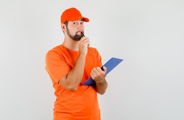 Bezorger met klembord en pen in oranje t-shirt, pet en peinzend kijkend. vooraanzicht.