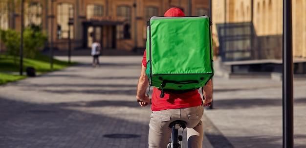 Bezorger met koelkasttas wegrijden op fiets