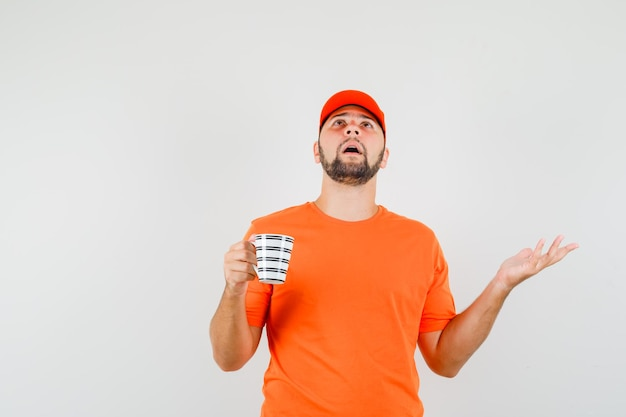 Bezorger met kopje drank in oranje t-shirt, pet en geïrriteerd, vooraanzicht.