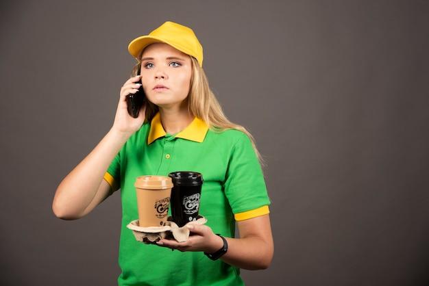 Bezorger met kopjes koffie spreken op smartphone.