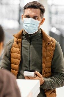 Bezorger met masker en klant betalen