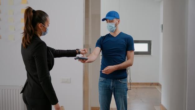 Bezorger met medisch gezichtsmasker en handschoenen tegen coronavirus die afhaalmaaltijden bezorgt in het bedrijfskantoor