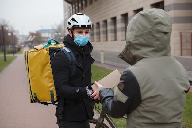 Bezorger met medisch masker levert kartonnen doos aan een klant, draagt medisch gezichtsmasker tijdens coronavirusquarantaine