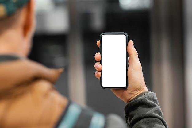 Bezorger met pakket bij lift met mobiel