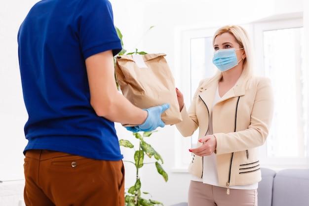 Bezorger met papieren zak met voedsel op witte achtergrond, voedselbezorger met beschermend masker en beschermende handschoenen