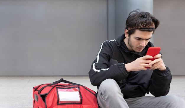 Bezorger met rode tas gebruikt zijn mobiele telefoon om de volgende bestelling te plaatsen, grijze achtergrond