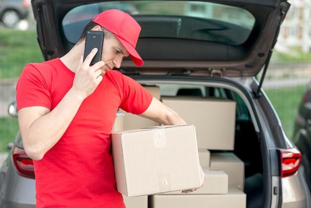 Bezorger met telefoon en doos