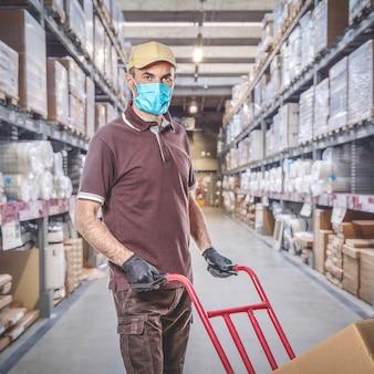 Bezorger met uniform en beschermend masker voor covid-19 in een magazijn. veilig verzendconcept.